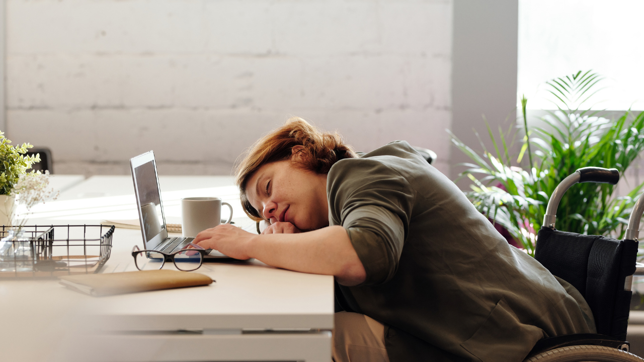 Tired woman in front of her desk sleeping