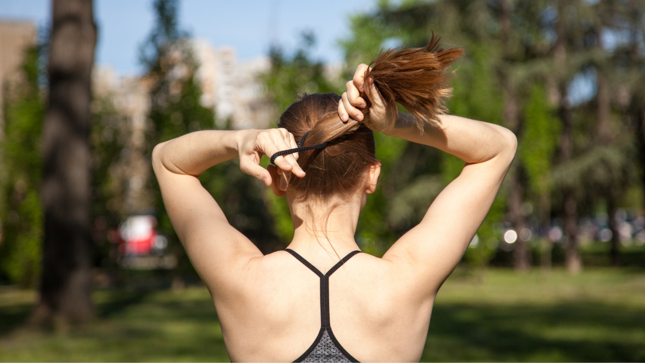Athletic woman putting hair in a ponytail preparing for dreams