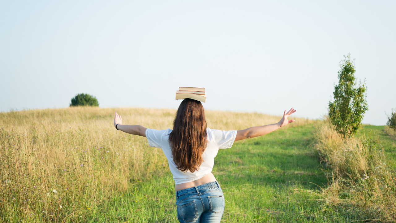 Woman in White Shirt Balancing with books on her head