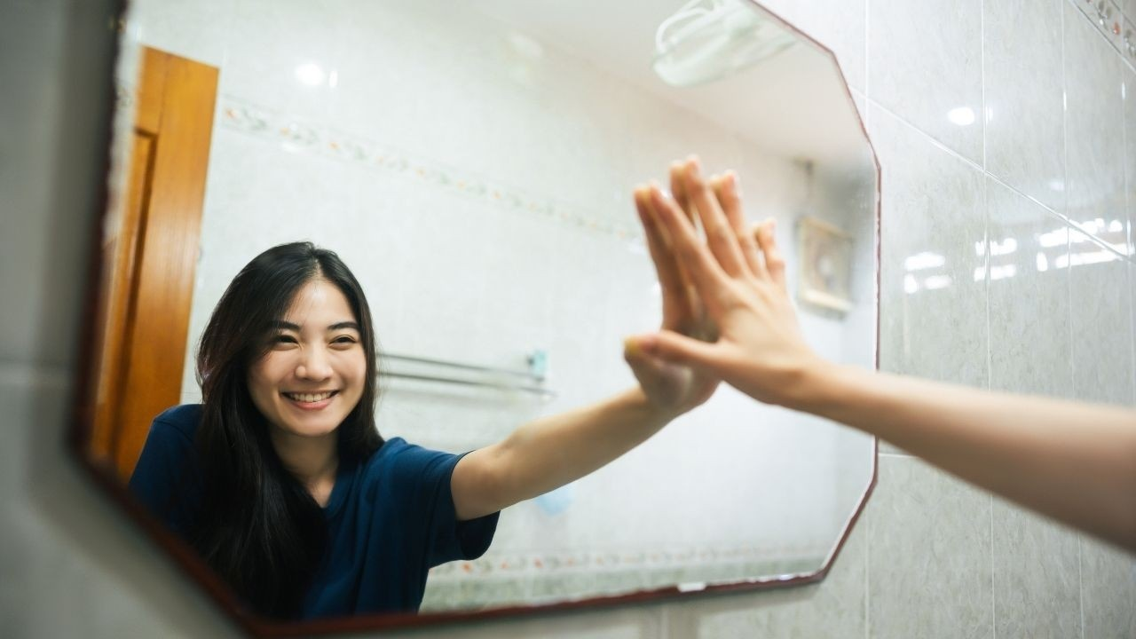 Positive Young Woman Looking at Self in the Mirror