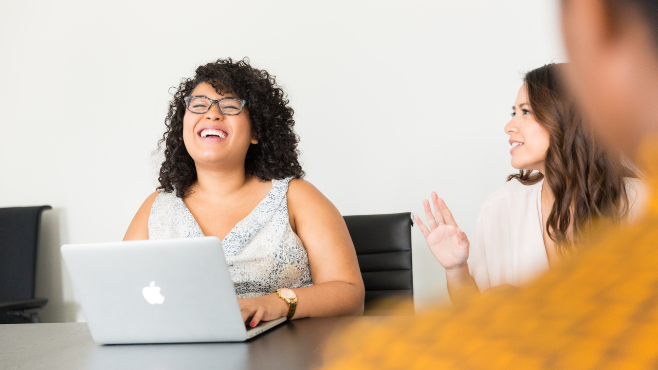 Two women laughing at a desk with a laptop.