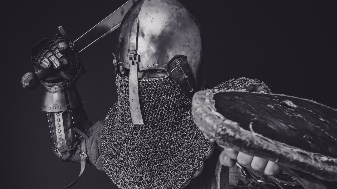Black and White picture of a medieval knight in armour with a sword and shield