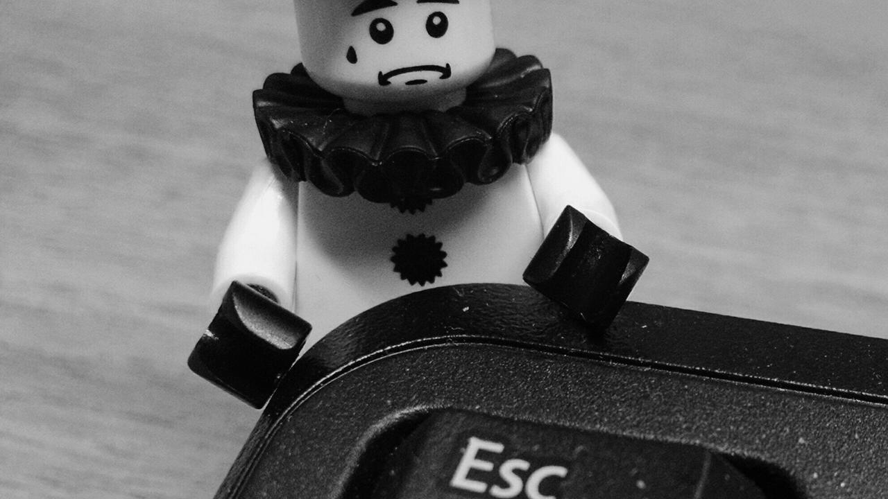 Black and white picture of a Lego person dressed as a clown with a sad face position beside a computer keyboard next to the ESC button
