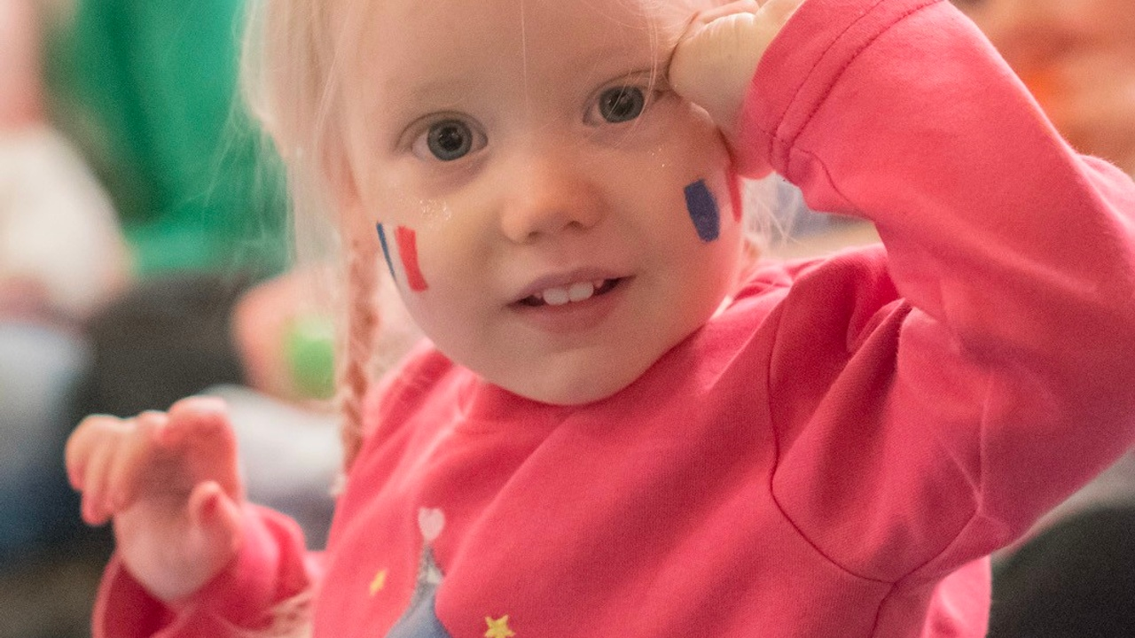 Little blonde girl with french flags on her cheeks having fun learning languages