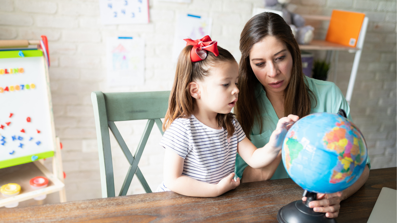 a mum and daughter looking at a globe