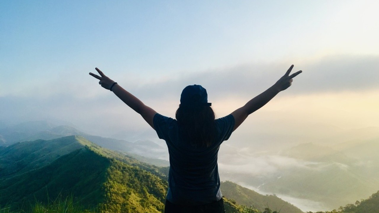 confident woman at the top of a mountain