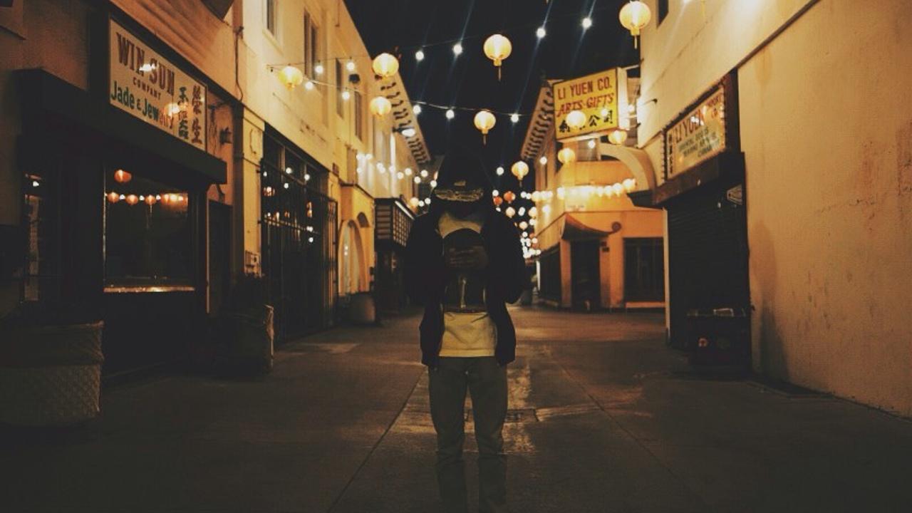 person in dark street lit up by lanterns