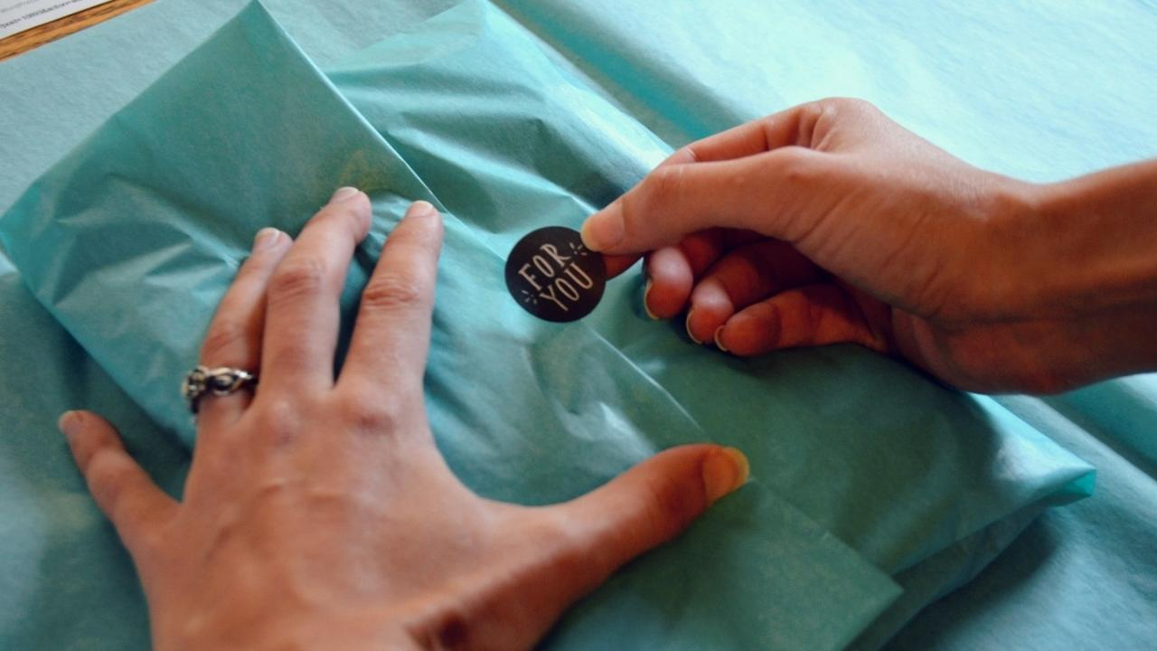 hand placing a thank you sticker on an order