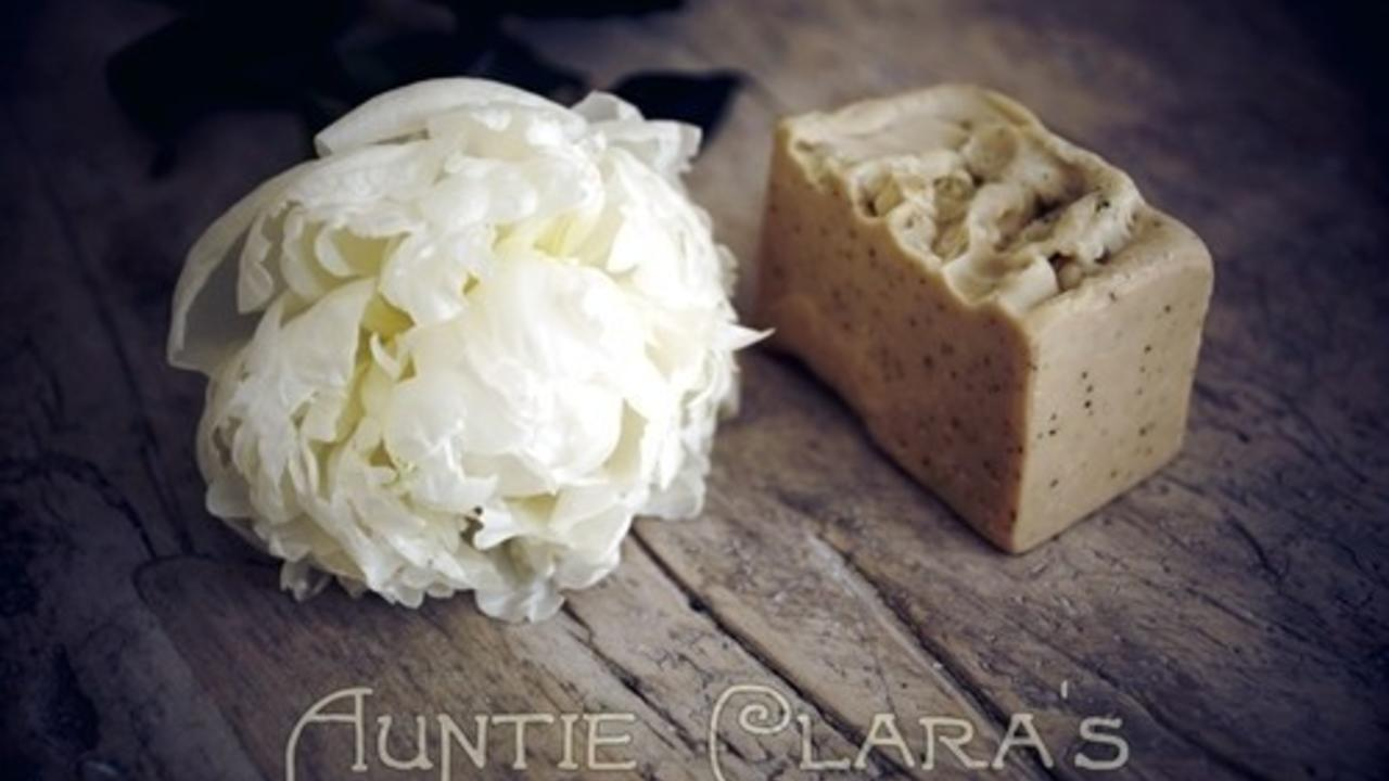 brown bar of soap next to a peony