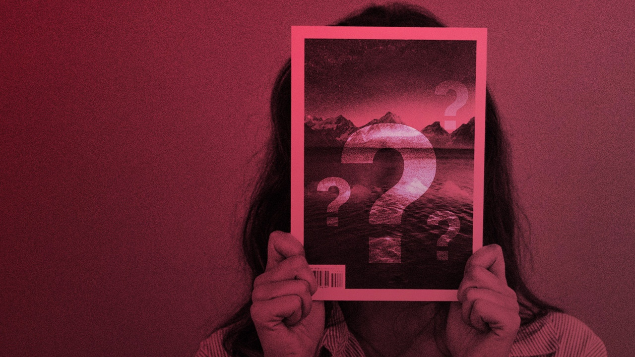 Woman holding picture with question marks in red