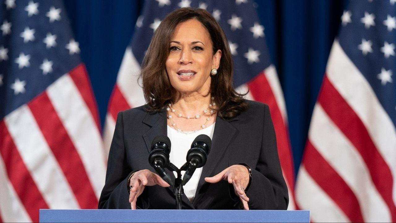 Kamala Harris speaking at a podium with American flags in the background