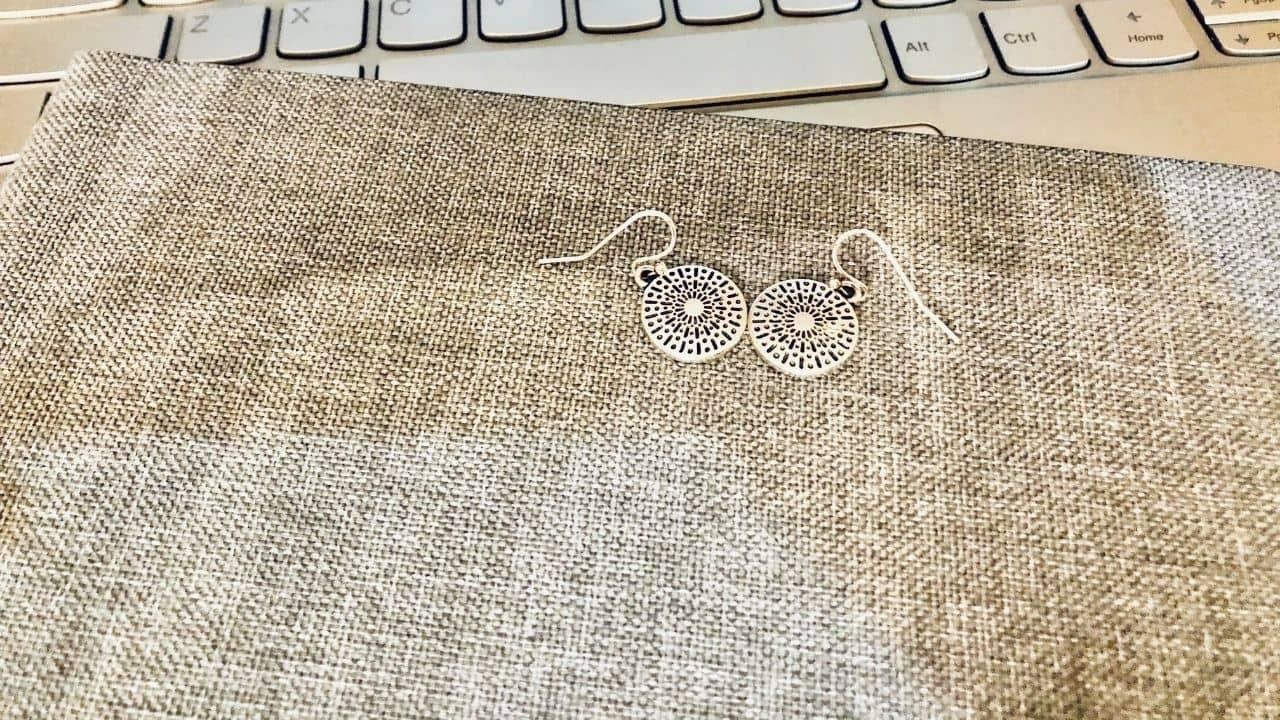 silver earrings on a notebook