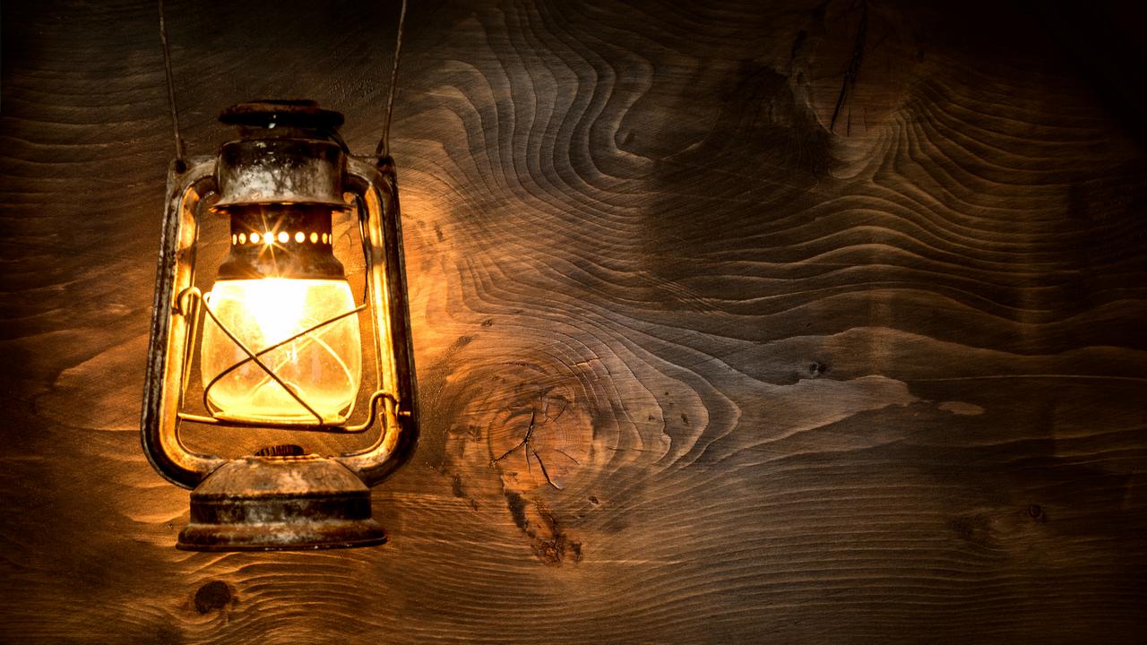 Lit lantern against wooden background