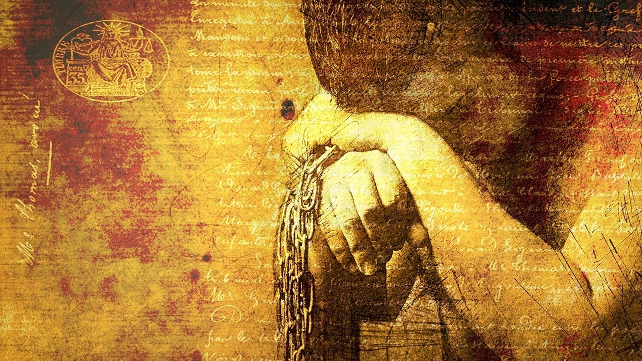 man in chains with his head on his hands