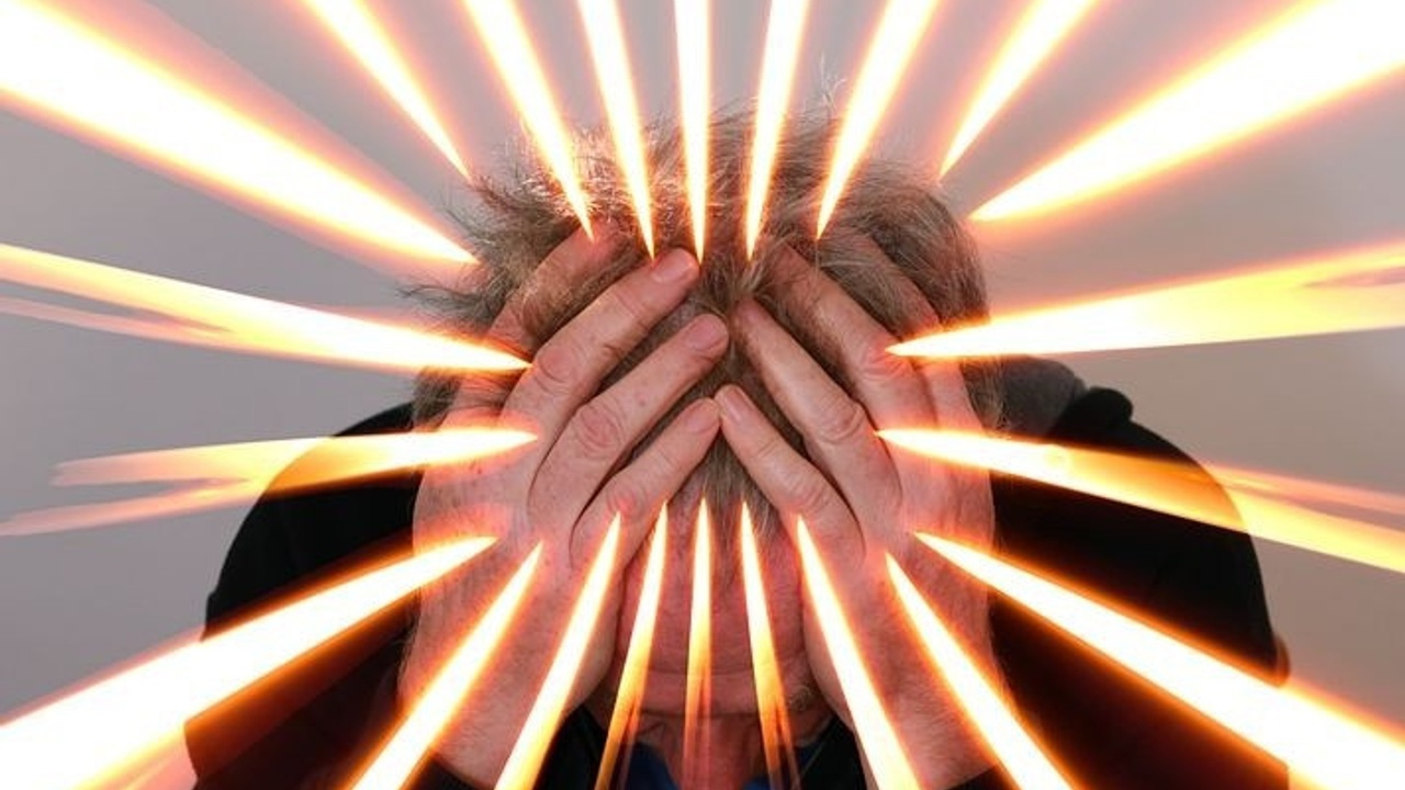 man with hands on head, light streaks on image