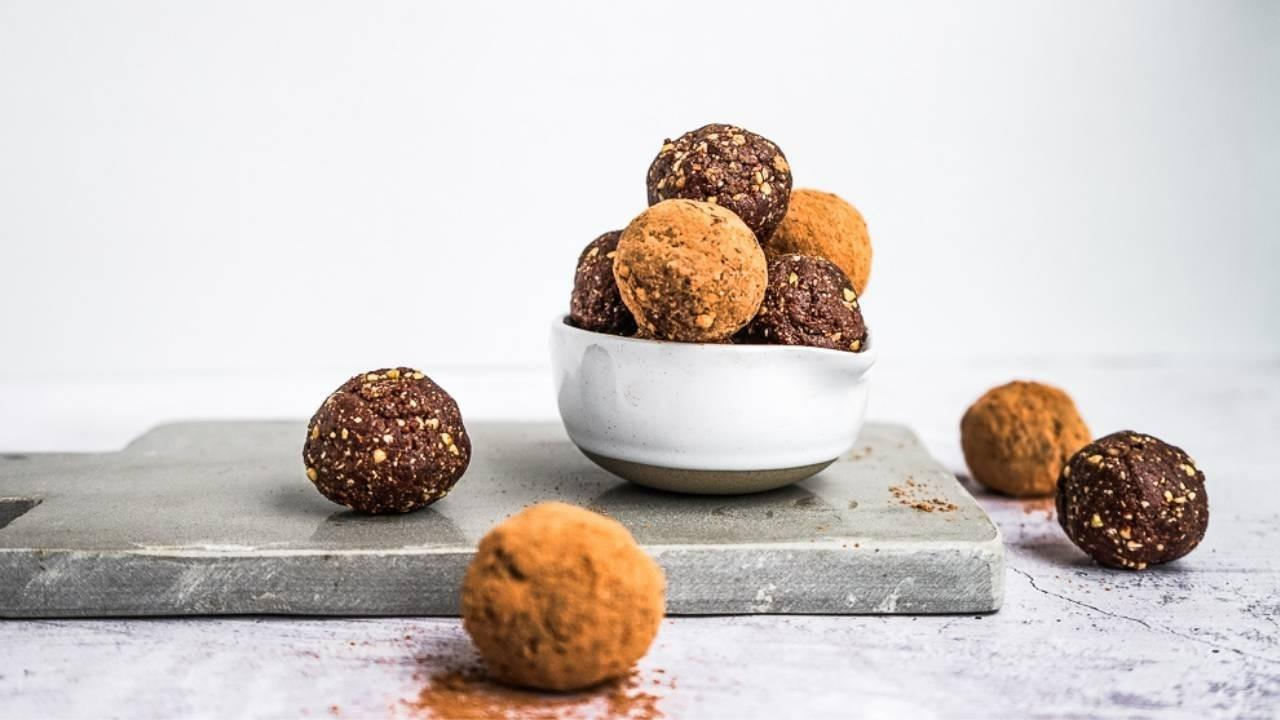 Coconut rough balls coated in cacao in a small measuring cup