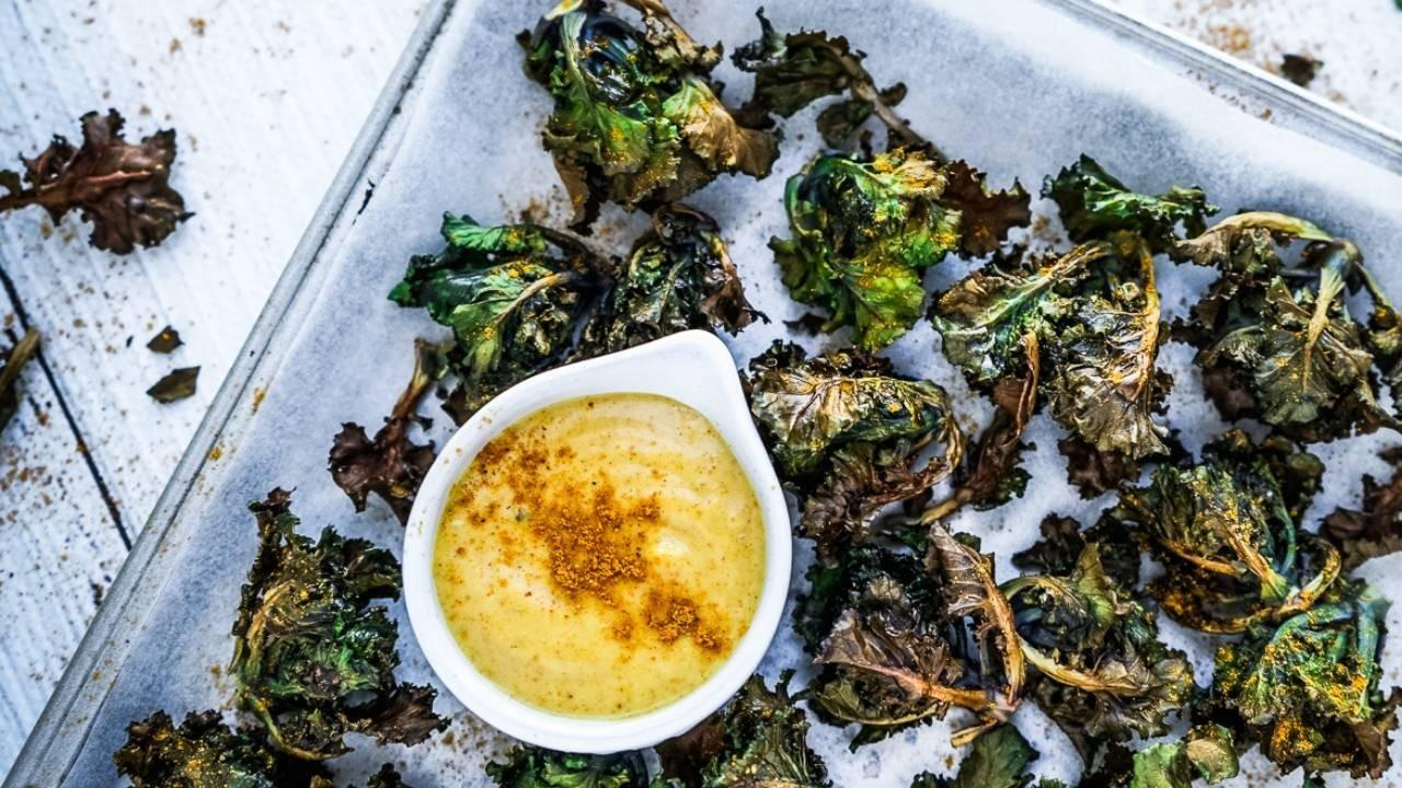 Baking tray of kalettes with a curry dipping sauce