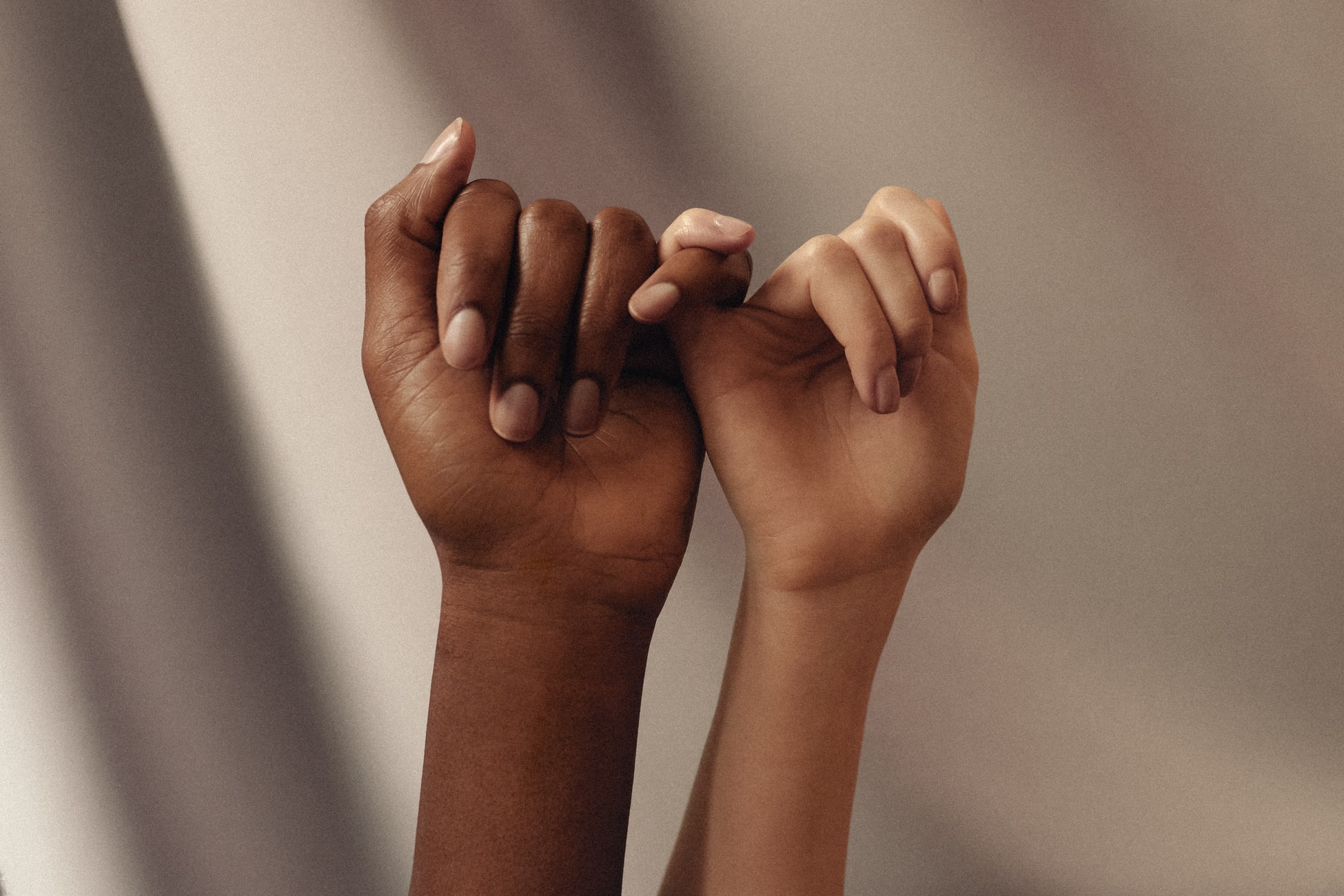 Two hands with pinky fingers entwined together
