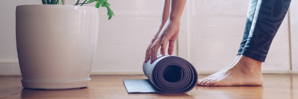A whole person rolling up a yoga mat after a holistic health exercise