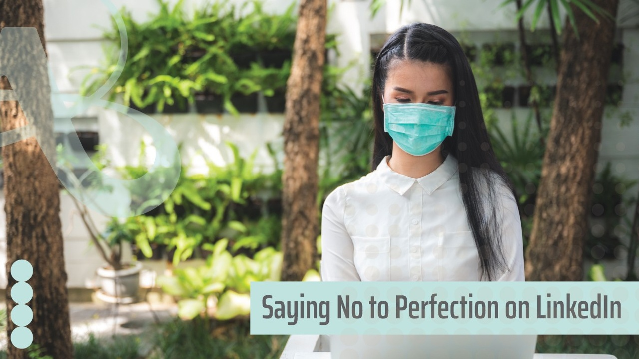 A woman in a white tailored shirt in an atrium looks down on her laptop screen. She is wearing a blue mask. The text reads, saying no to perfection on LinkedIn.