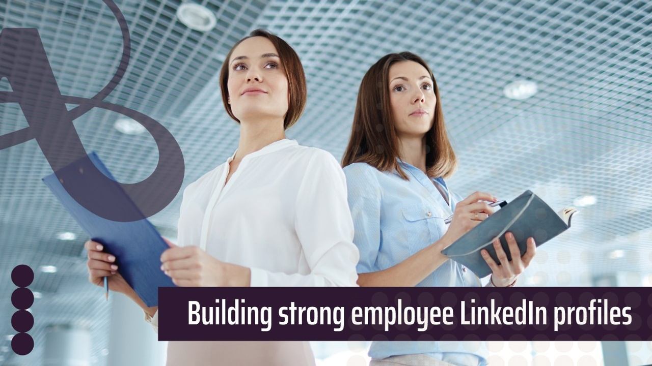 Two women are standing next to each other. They're both holding notebooks and have confident expressions on their faces. The text reads, building strong employee LinkedIn profiles
