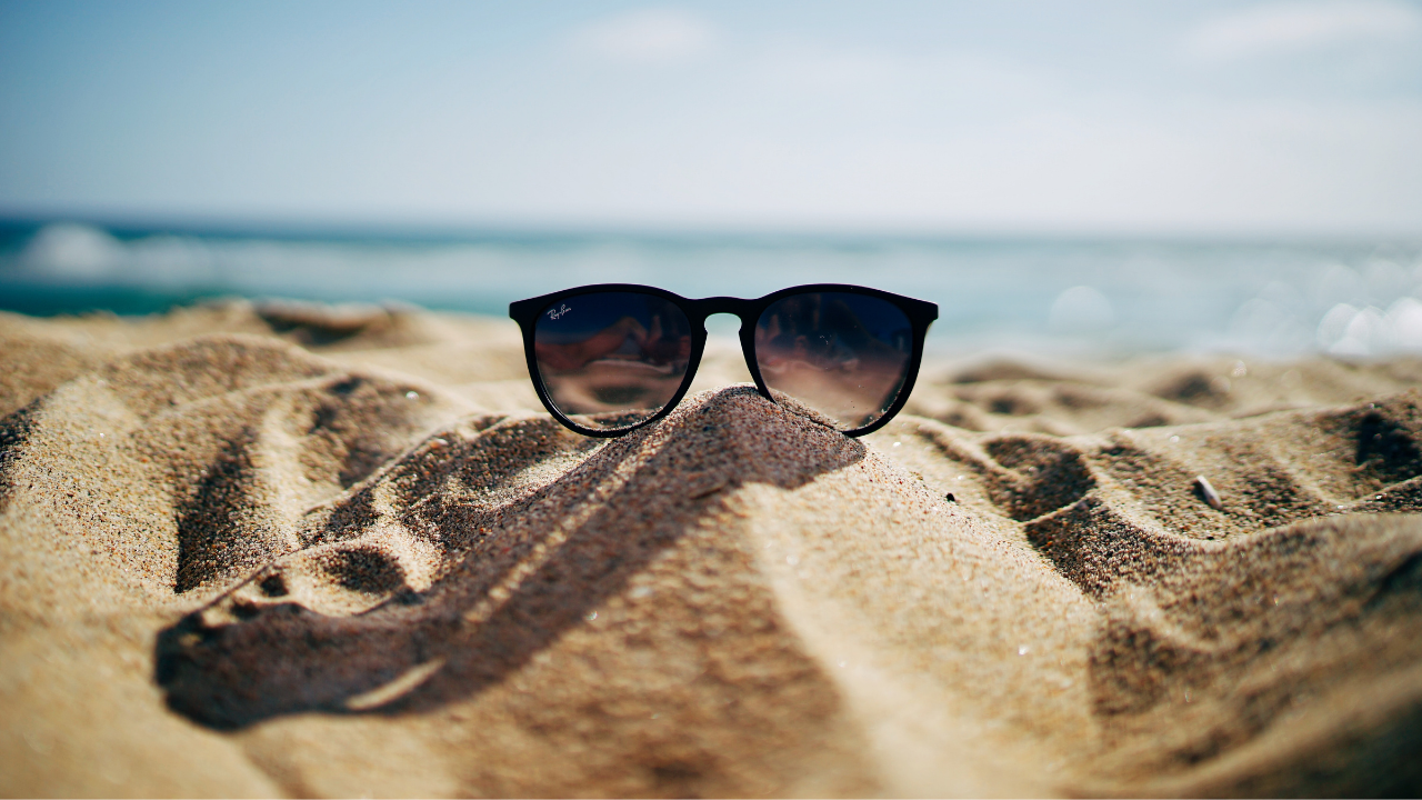 image of sunglasses in the sand at the beach