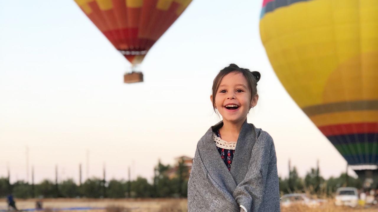 image of delighted girl in front of hot air balloons