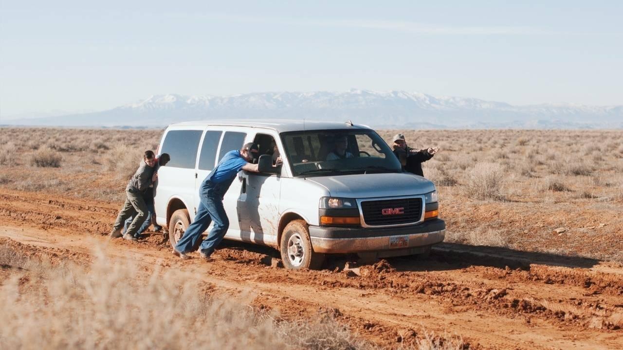 men pushing a van stuck in mud