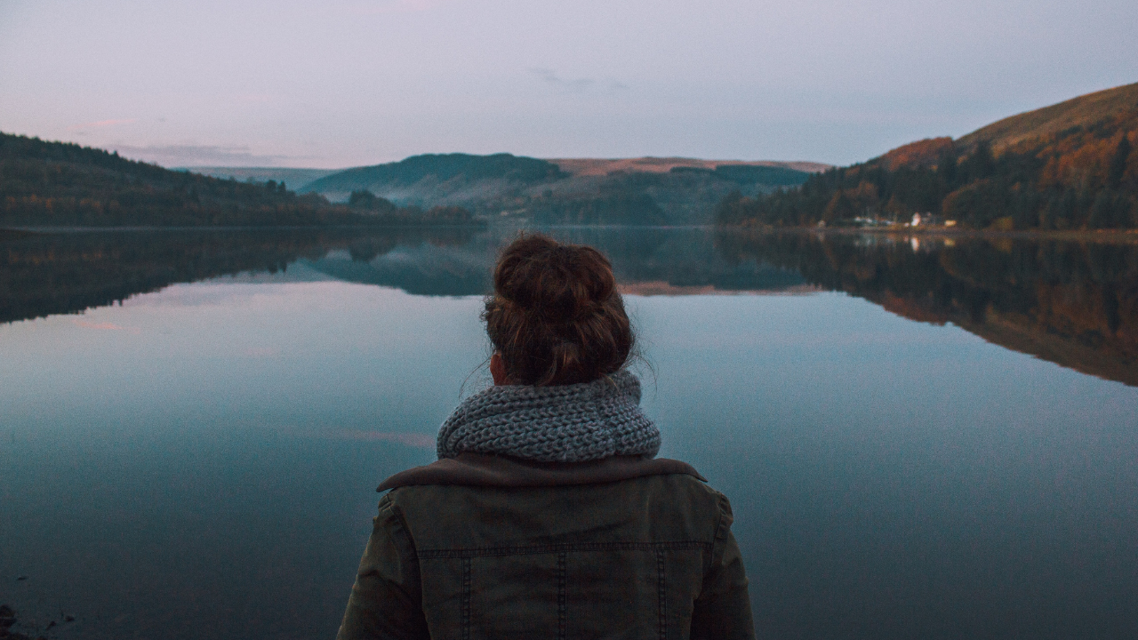 image of woman looking out on a lake