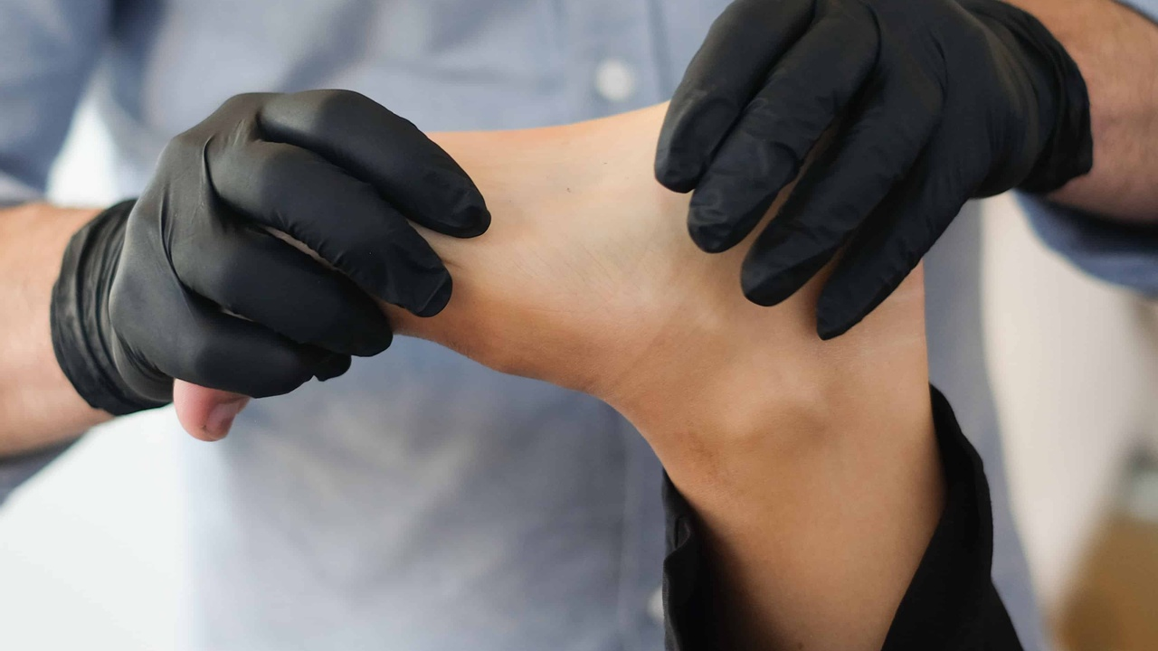 gloved chiropractor or physical therapist manipulates a foot
