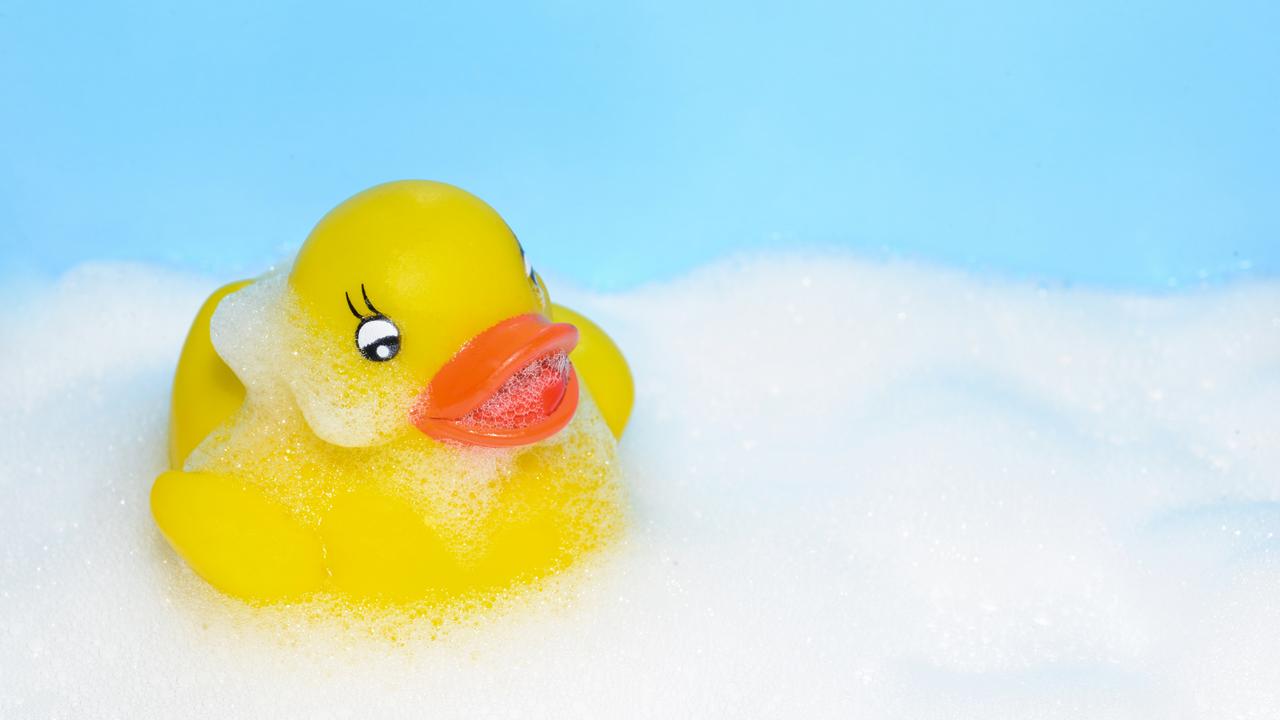 Yellow rubber duck on bath bubbles in a bathtub
