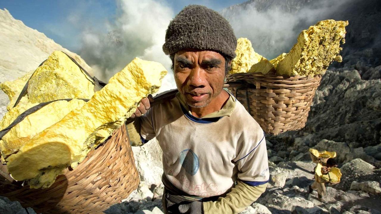 Artisanal sulfur miner working in an active volcano in Indonesia