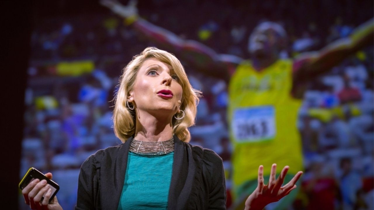 Dr. Amy Cuddy giving a TED Talk on confident body language.