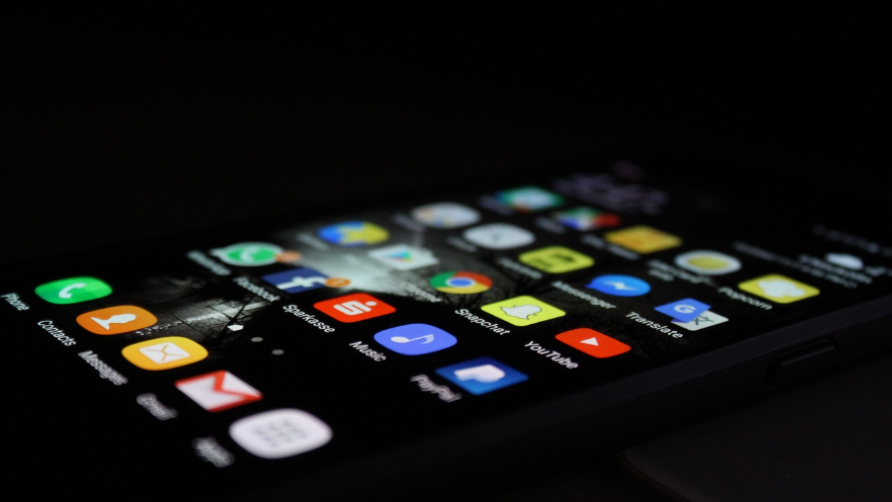 iPhone in black background with many apps on home screen