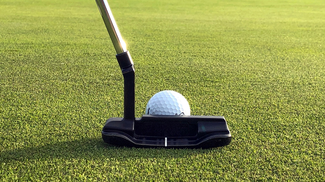A putter is lined up ready to strike a golf ball on the grass.