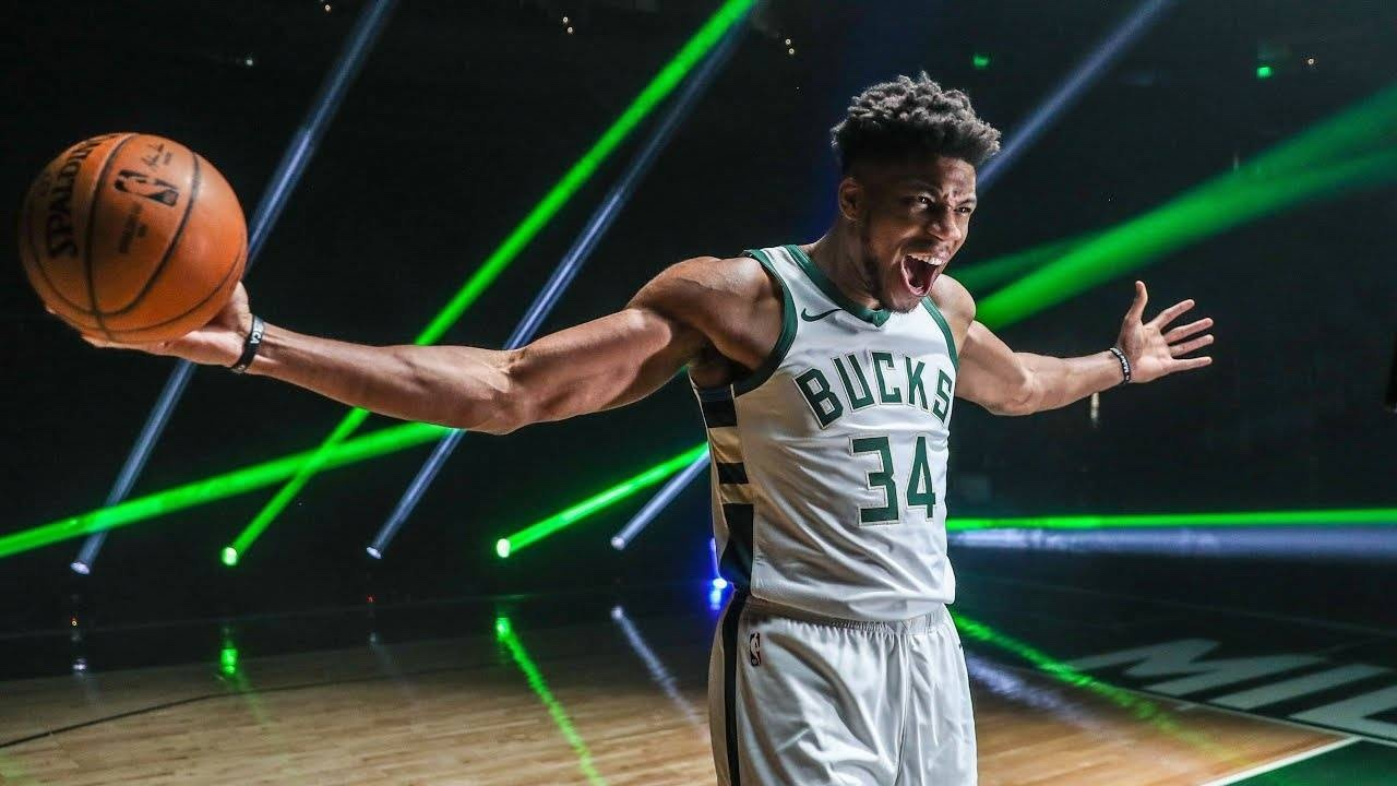 Giannis Antetokounmpo of the Milwaukee Bucks extends his arms while holding a basketball in one hand.