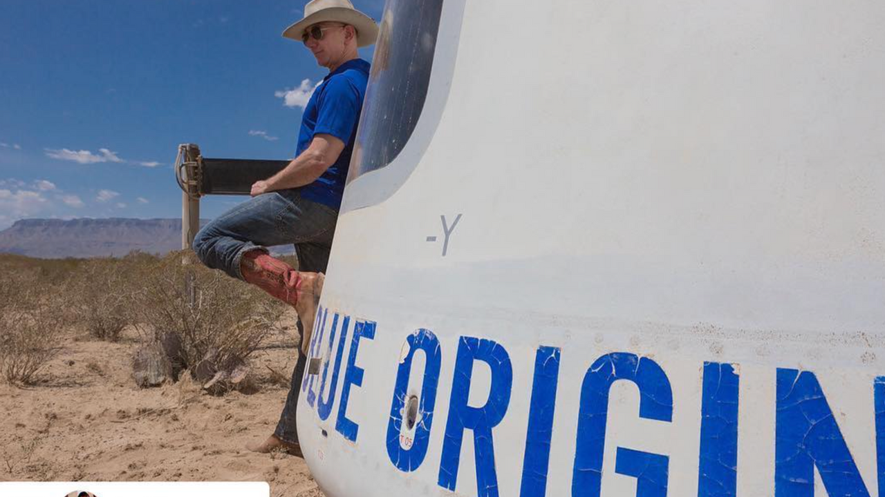 Jeff Bezos wearing his lucky boots poses beside a Blue Origin spacecraft in the desert