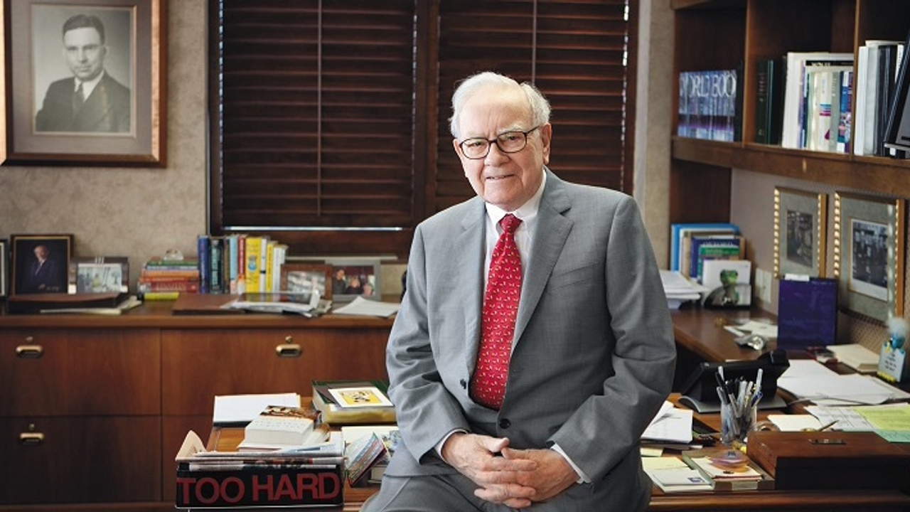 Warren Buffett wearing a suit and tie and sitting on the front of his desk