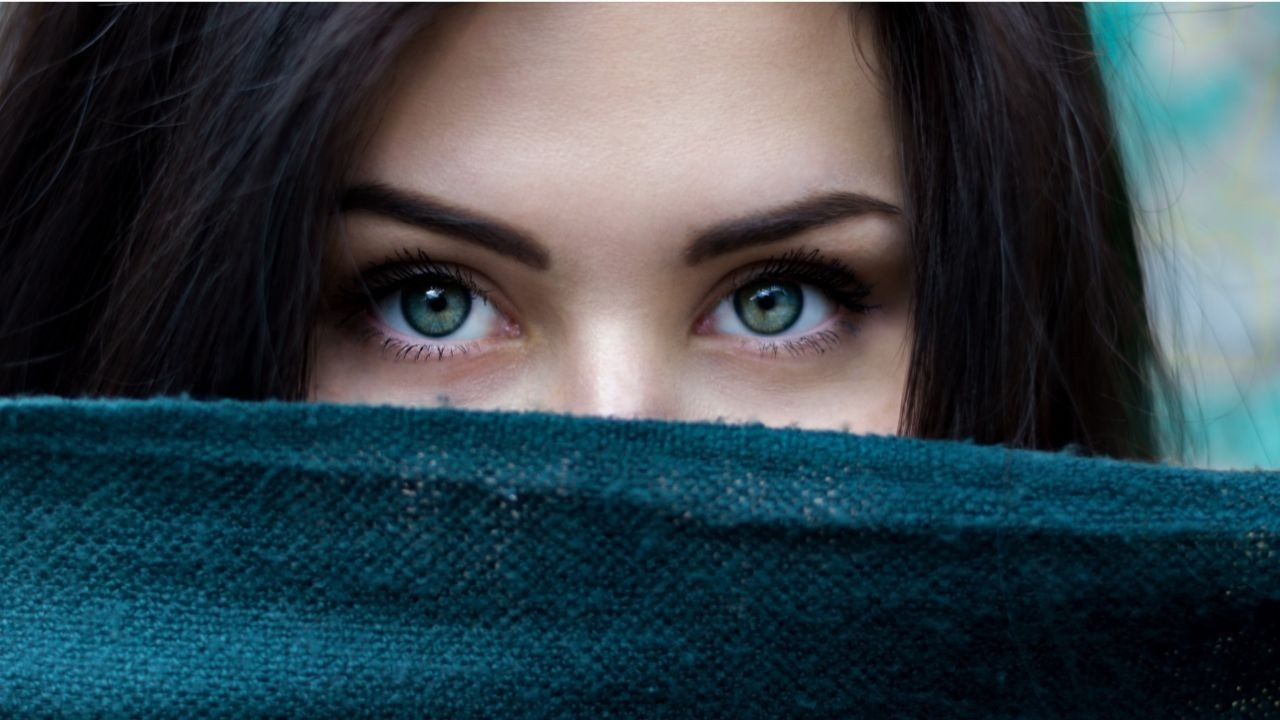 Woman with blue eyes staring at the camera, with a cloth cover the lower part of her face