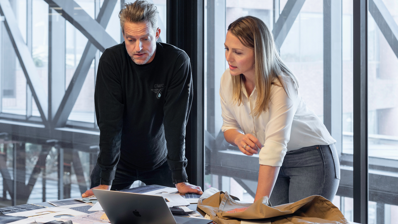 man and woman looking at designs on a computer on a table with fabric scraps