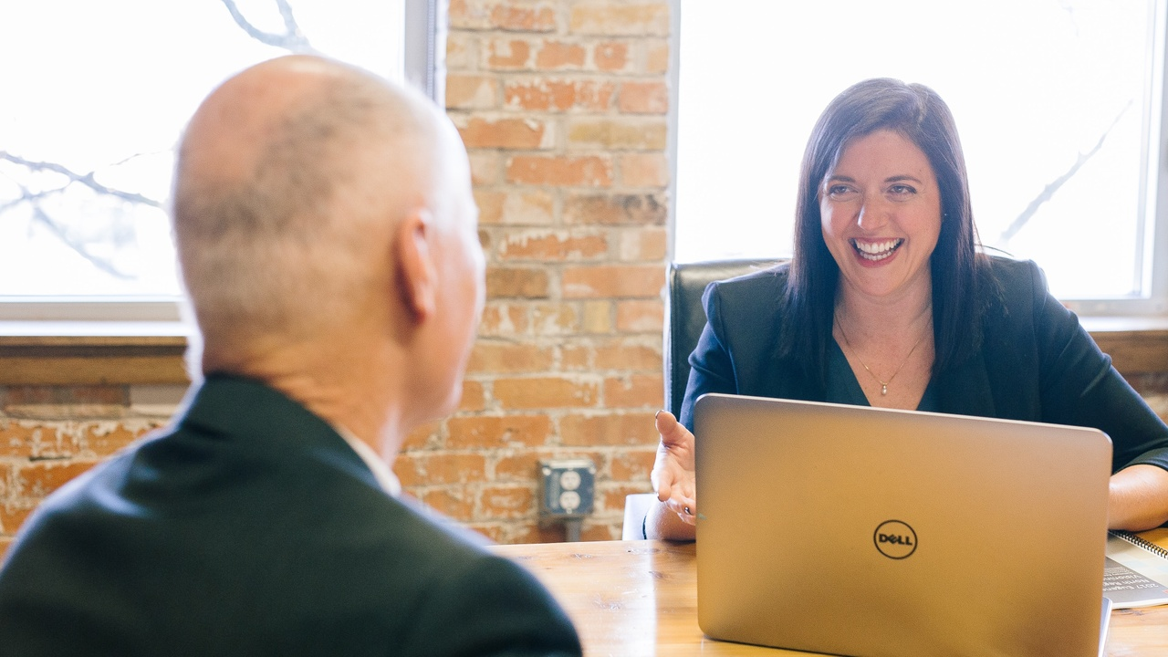 Young woman with a computer providing leadership to a man sitting across the table from her.