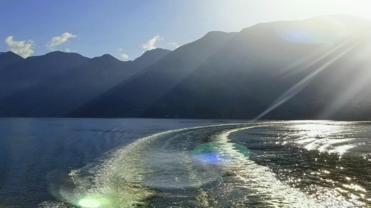 water waves on the deep blue ocean representing peace and tranquility with the hills in the shadow over the bright sky