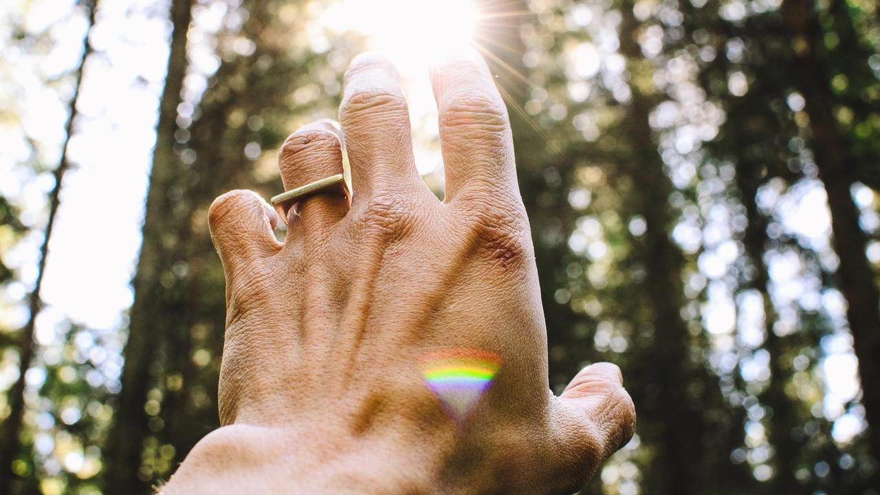 a man raising his hand to the light with a rainbow prism effect on the reflection.