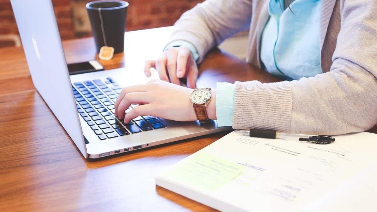 Mujer en su computadora tomando notas