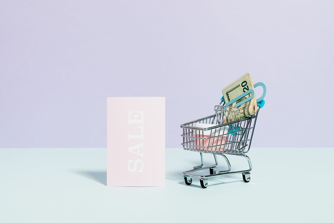 carrito-de-compras-con-billetes-y-cartel-que-dice-sale