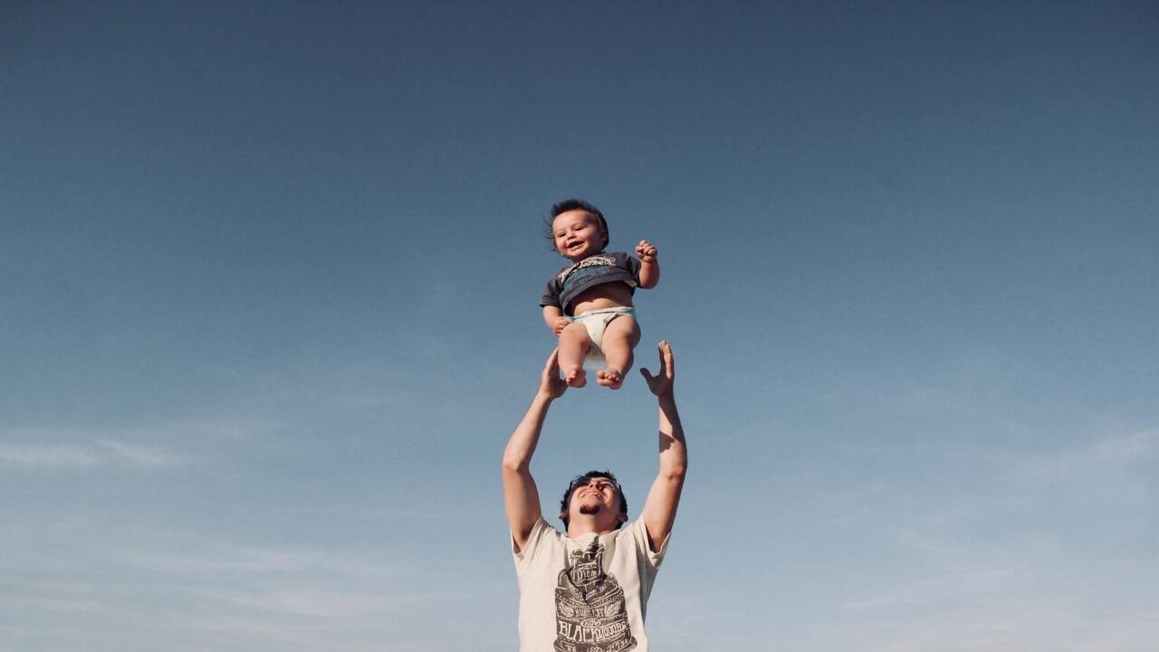 Padre levantando a su hijo en el día del padre