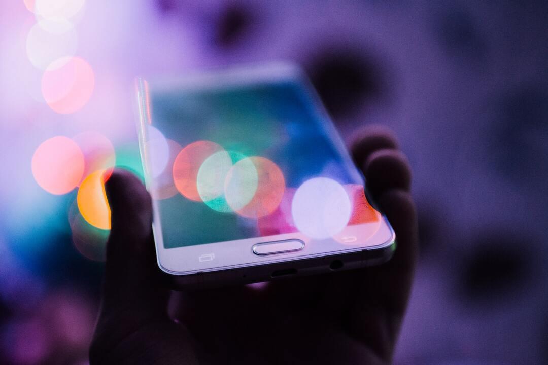 Teléfono con luces de colores reflejadas en la pantalla