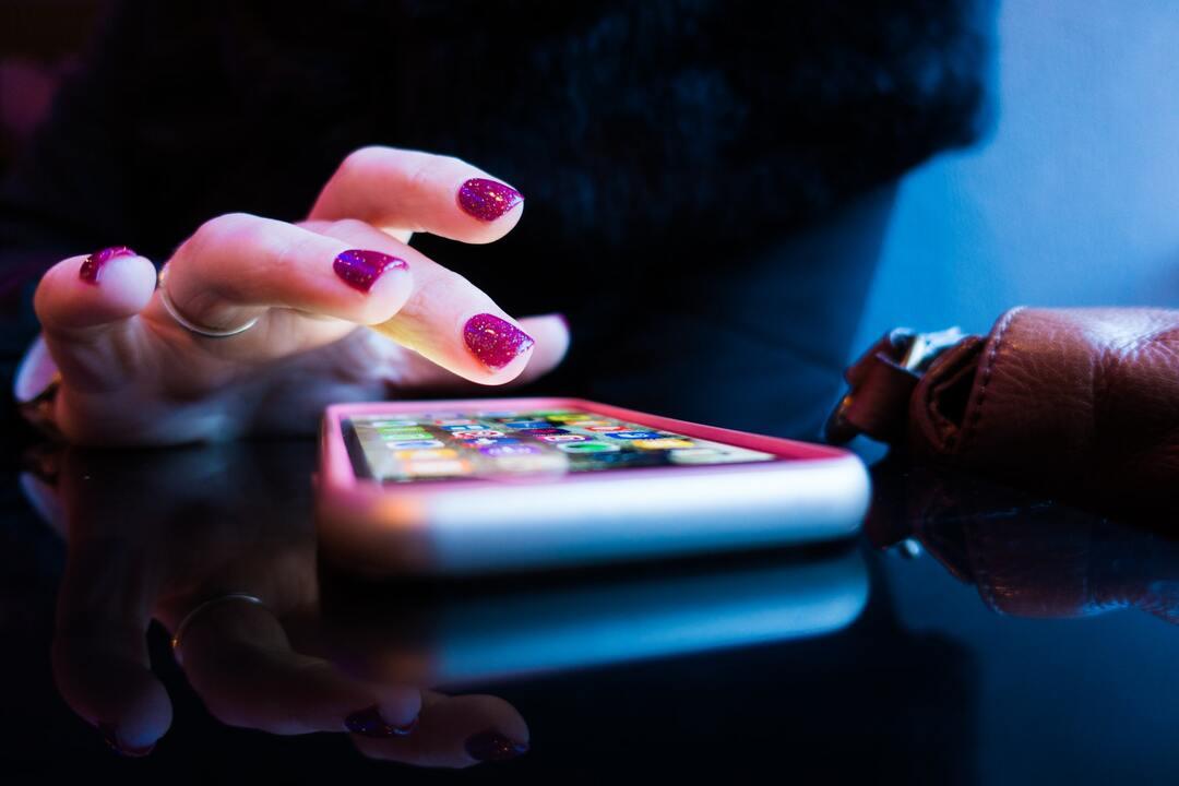 Persona usando su teléfono sobre una mesa