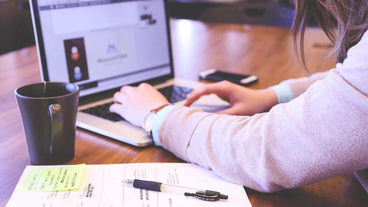 Mujer escribiendo en una computadora y con su cuaderno tomando nota.