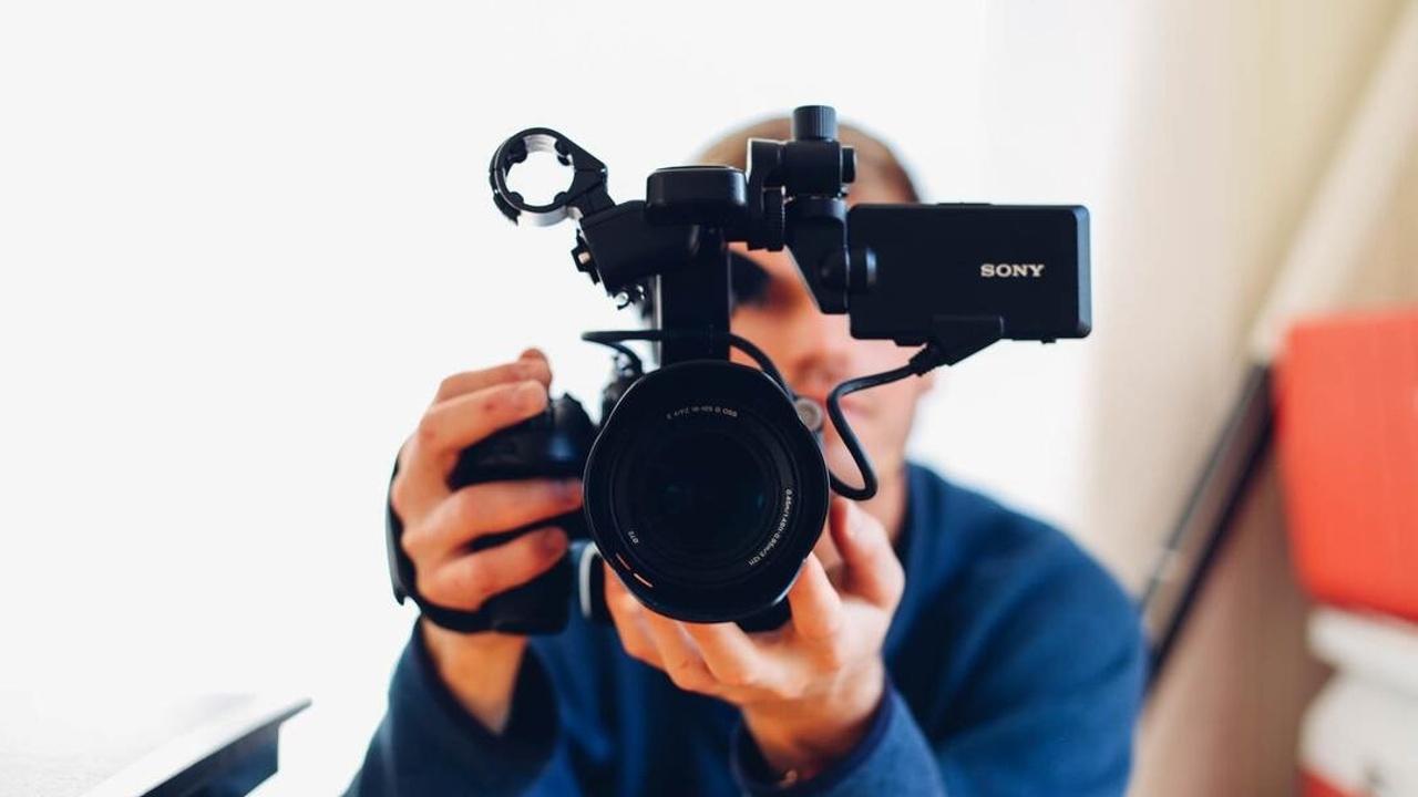 Hombre apuntando una cámara hacia la cámara